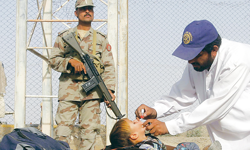 CHAMAN: A health worker gives polio vaccine drops to a child going to Afghanistan in this border town on Monday.—INP