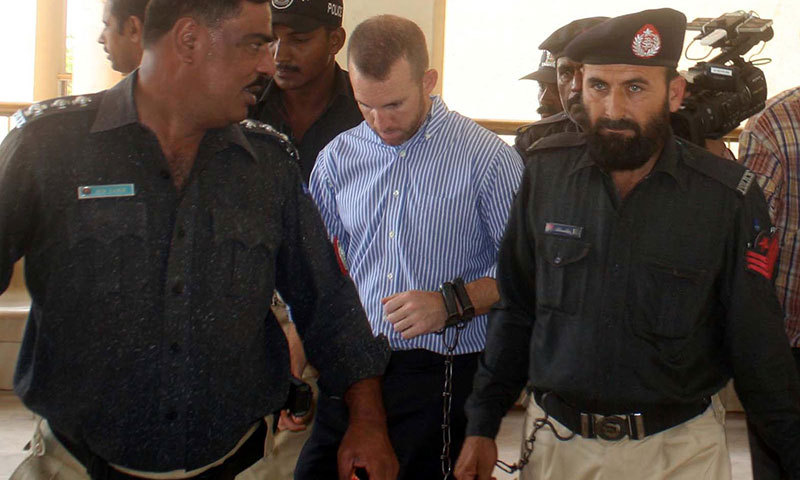 Police escorting the US national to a local court in Karachi. — Photo by INP