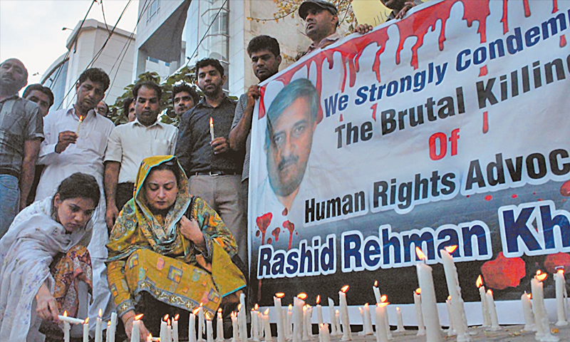 MULTAN: Rights activists light candles during a demonstration to condemn the killing of Rashid Rahman.—INP