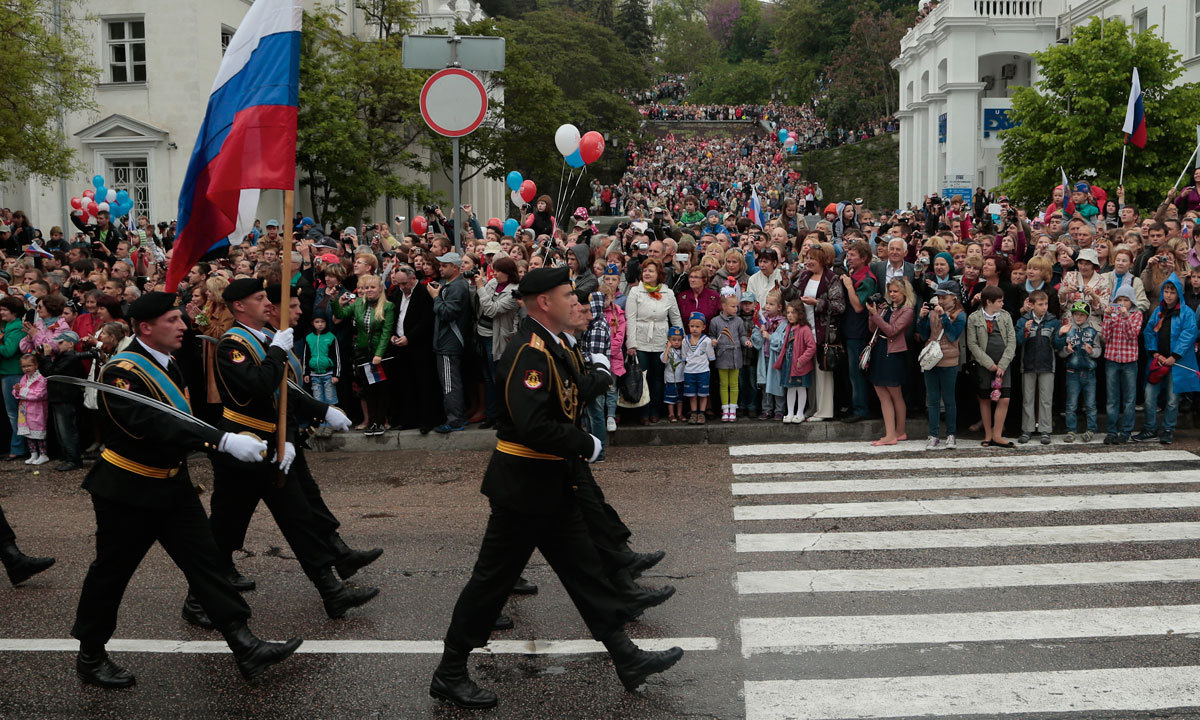 Russian marines carry national flag as local residents gather along the street during a Victory Day military parade, which commemorates the 1945 defeat of Nazi Germany, in Sevastopol, Russia, on Friday, May 9. – Photo by AP