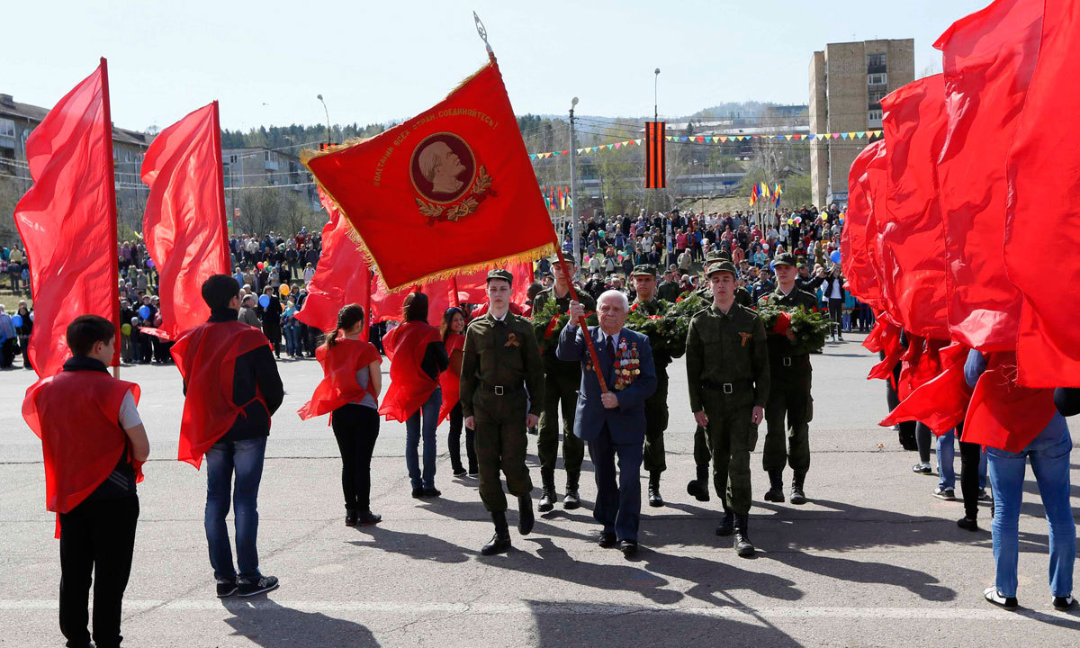 Russian World War Two veteran Alexey Samokhin (Centre), 89, carries a red flag as he leads a procession during the Victory Day celebration in Divnogorsk, near Russia's Siberian city of Krasnoyarsk, May 9. – Photo by Reuters