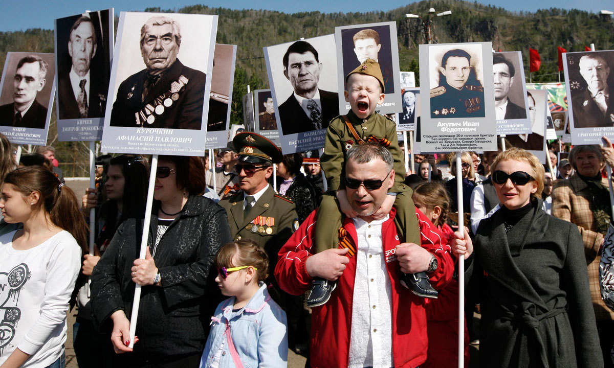 People carrying portraits of deceased relatives who took part in World War Two, march in a parade during Victory Day commemorations in the town of Divnogorsk, near Russia's Siberian city of Krasnoyarsk. – Photo by Reuters