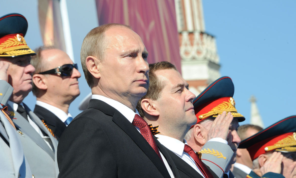 Russia's President Vladimir Putin (2nd Left) and Prime Minister Dmitry Medvedev (3rd Left) attend a Victory Day parade at the Red Square in Moscow, on May 9, 2014. – Photo by AFP