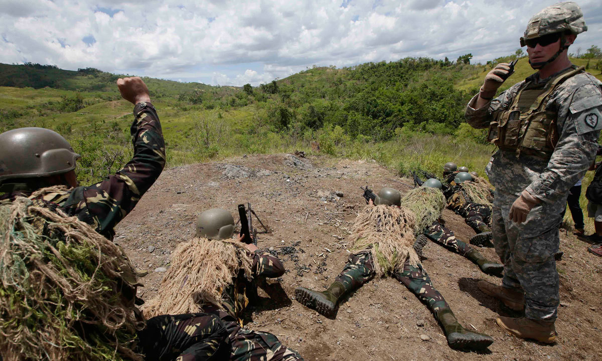 A US Army officer, right, watches as his Philippine counterpart fire their weapons to simulate a raid during the live-fire joint US-Philippines military exercise dubbed Balikatan 2014, Saturday, May 10, 2014 at the Philippine Army training camp, Fort Magsaysay, in northern Philippines. – Photo by AP