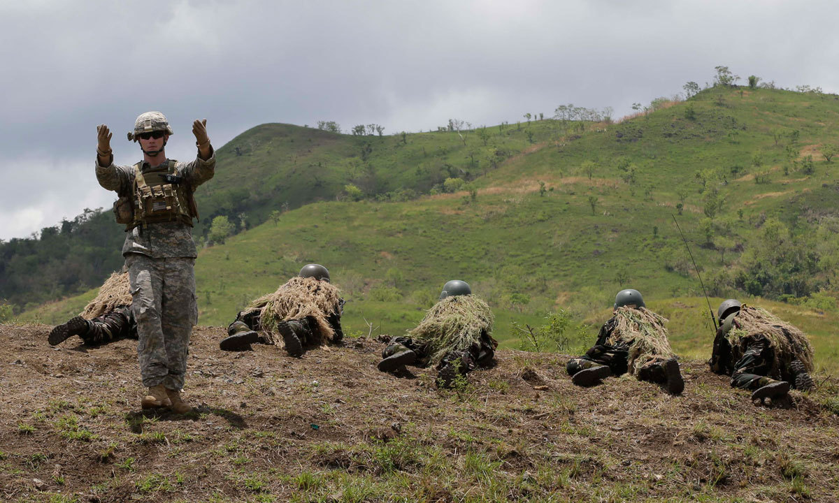 A US Army officer gestures as his Philippine counterpart prepare to fire their weapons in a live-fire exercise at the ongoing joint US-Philippines military exercise dubbed Balikatan 2014, Saturday, May 10, 2014 at the Philippine Army training camp at Fort Magsaysay, Nueva Ecija province in northern Philippines. – Photo by AP