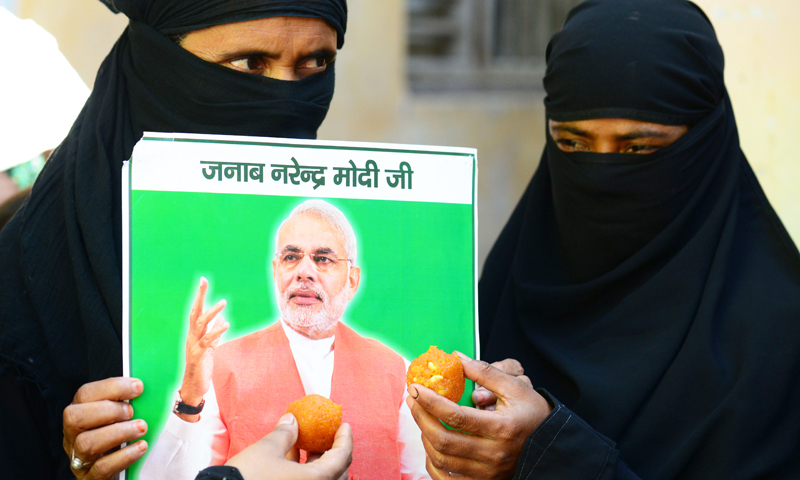 Indian Muslim supporters hold up sweets and a portrait of victorious Bharatiya Janata Party (BJP) prime ministerial candidate Narendra Modi. - AFP