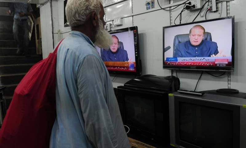 Photo shows a man watching a television screen tuned to Geo News.—File Photo