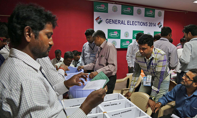 An Indian election official opens postal ballots to count votes at a polling station in Hyderabad, India, Friday, May 16, 2014. India