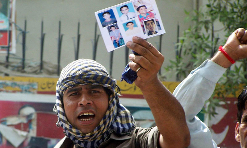 A relative of missing Hindu boys holds their pictures to protest outside Hyderabad Press Club on Saturday. – INP Photo