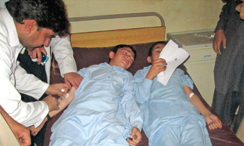 Two students undergo treatment at a hospital in Swat after getting anti-measles vaccine. — Dawn