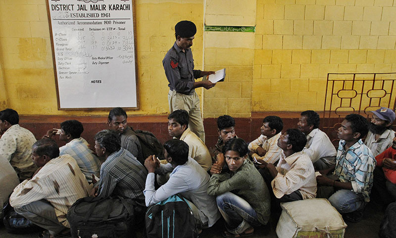 A Pakistani police officer checks the documents of an Indian fishermen waiting for their release from a prison in Karachi, Pakistan, Sunday, May 25, 2014. — Photo by AP