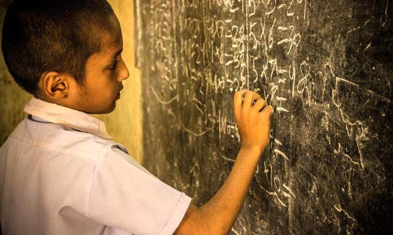 A boy practicing math on a blackboard during a lecture at Jufelhurst School in Karachi. —Photo by Shameen Khan