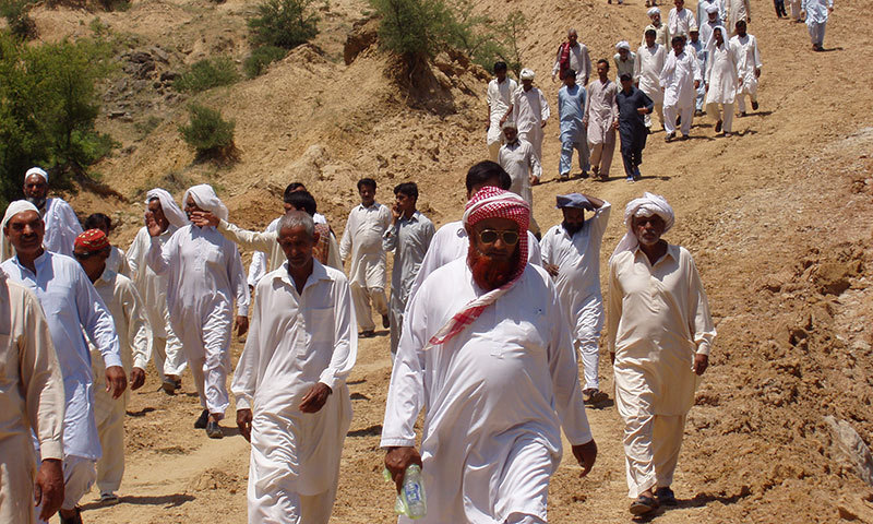 Villagers head towards the site of the road construction in protest against the forest and wildlife department. -Dawn