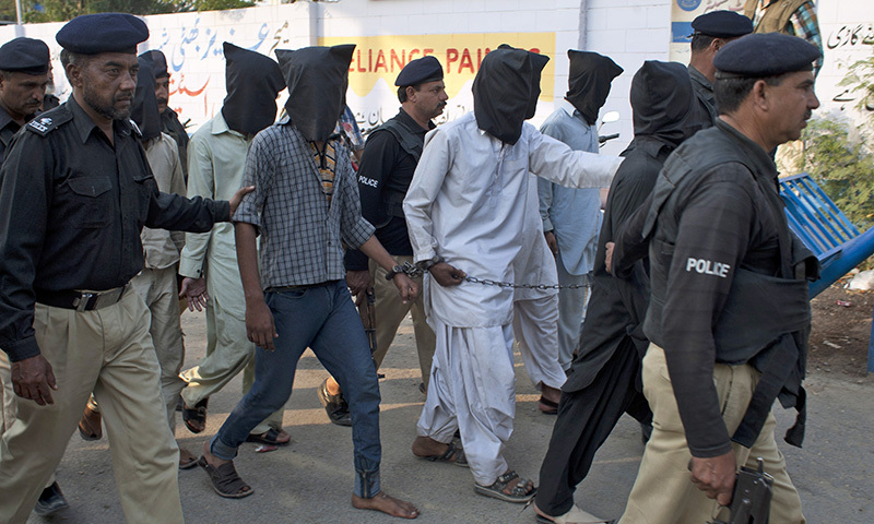 In this March 7, 2014 photo, police officers escort alleged criminals arrested during an operation in Karachi. — Photo by AP