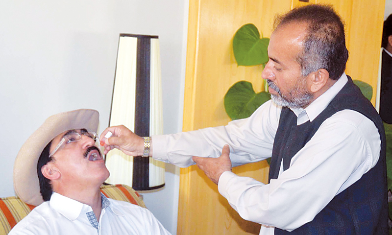 QUETTA: A health worker administers polio drops to a passenger at the airport here on Saturday.—PPI