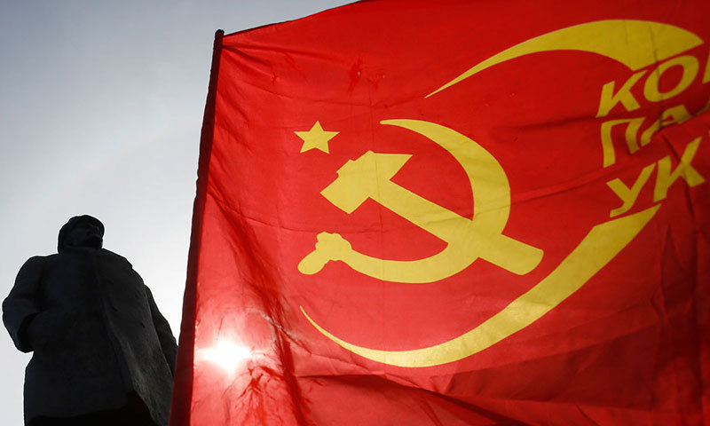 A man waves a communists flag in front of the monument of Soviet Union founder Vladimir Lenin, during a Victory Day celebration. – Photo by AP