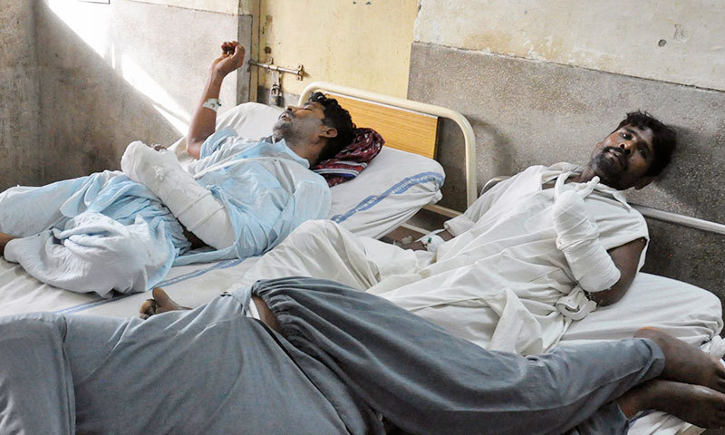 Ghulam Mustafa (rear R), 38, and Liaquat Ali (rear L), 42, lie on beds after being brought to the Victoria Hospital for treatment in Bahawalpur June 2, 2014. – Reuters Photo