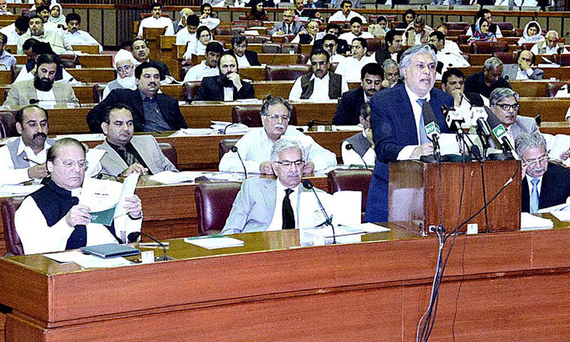 Prime Minister Nawaz Sharif studies the Federal Budget 2014-15 proposal documents while Finance Minister Ishaq Dar speaks in National Assembly on Tuesday. – APP Photo