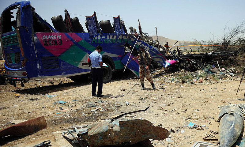 Security personnel stand beside the wreckage of a bus after a Pakistan air force fighter plane crashed at a bus terminal on the outskirts of Karachi on June 3, 2014. — Photo by AFP