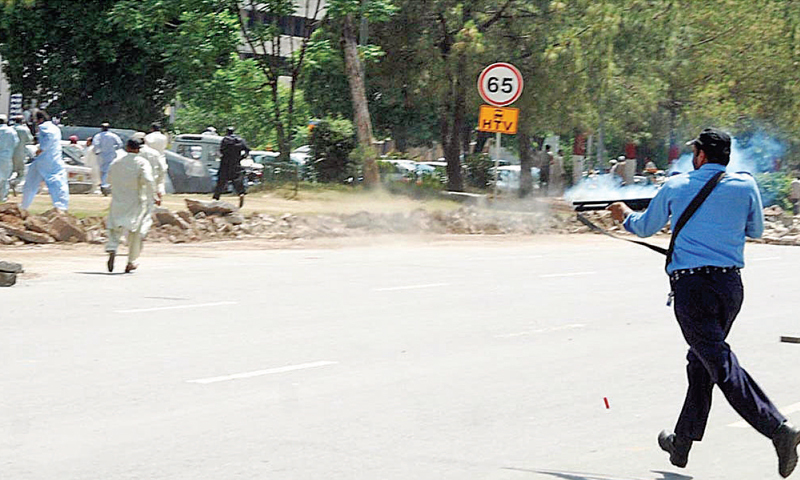A policeman fires rubber bullets at protesters in Islamabad on Wednesday. — Online
