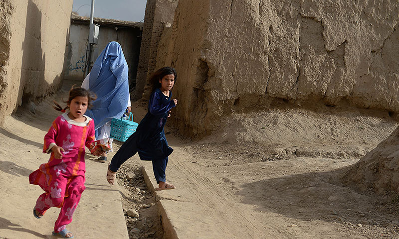 In this photograph taken on June 5, 2014, Afghan children play near a collection of destroyed buildings in the village of Deh Saqi on The Shomali Plains some 20 kms north of Kabul. – AFP Photo