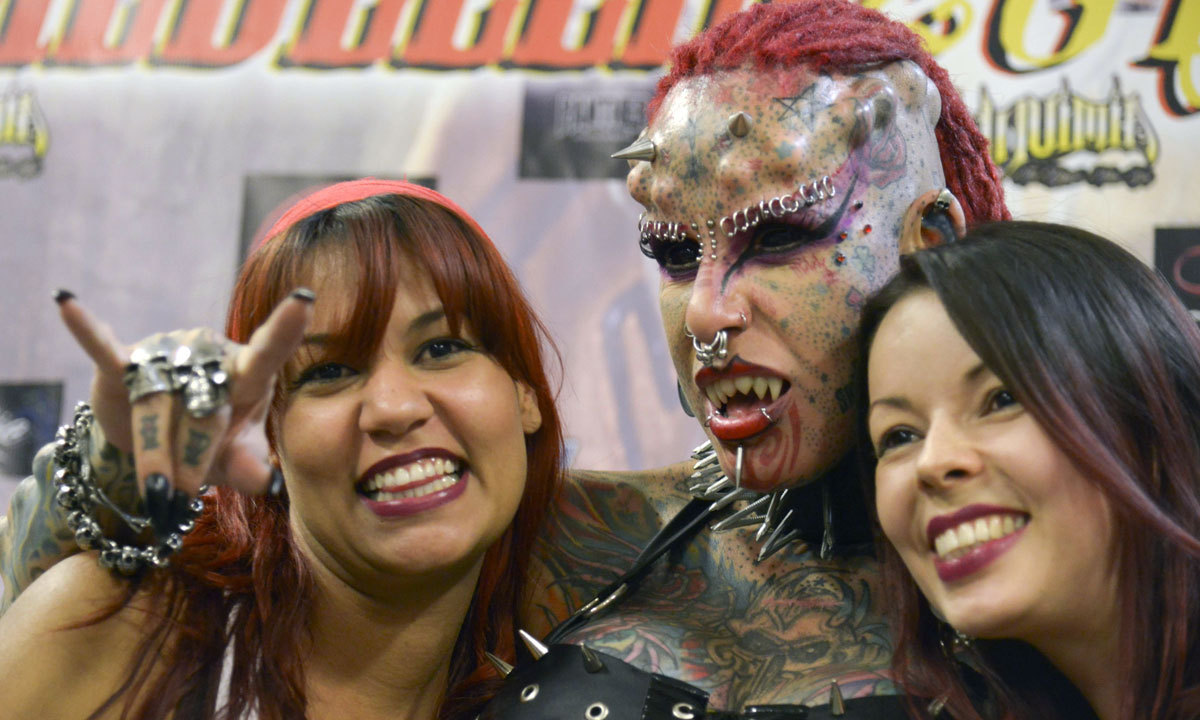 """""""The Vampire Woman""""(Center) poses with visitors during the Fifth Expotattoo Colombia, in Medellin, Antioquia department. AFP"""