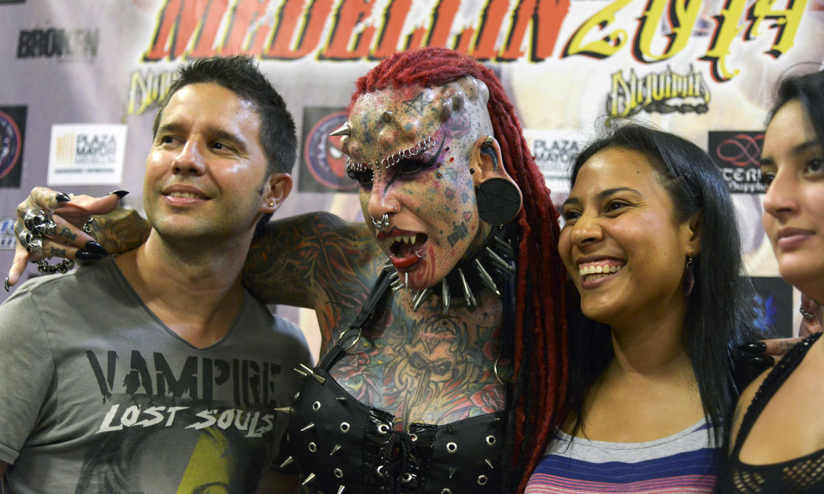 """""""The Vampire Woman""""(2nd-Left) poses with visitors during the Fifth Expotattoo Colombia, in Medellin, Antioquia department. AFP"""