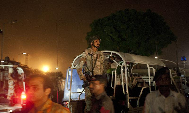 Pakistani security troops rush to Karachi airport terminal following attacks by unknown gunmen. -AP Photo