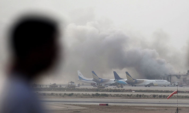 A man watches as smoke rises after militants launched an early morning assault at Jinnah International Airport in Karachi on June 9, 2014. — Photo by AFP