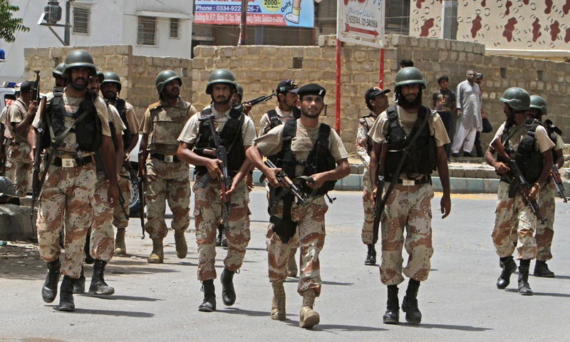 Security personnel inspect the site around a training center after gunmen attacked the facility in Karachi on Tuesday.  - AP