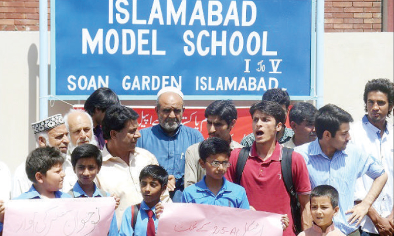 Residents of Soan Garden protest outside Islamabad Model School, seeking regular classes in the institution.