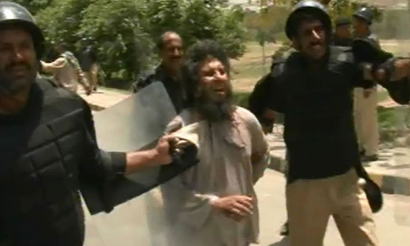 A view of a protester being arrested by police personnel.  — DawnNews screengrab