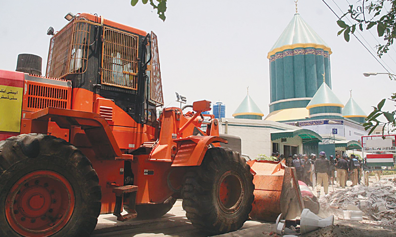 LAHORE: A police bulldozer removing barricades outside Dr Tahirul Qadri's Minhajul Quran headquarters in Model Town on Tuesday.—INP
