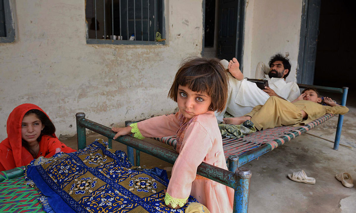 An internally displaced family from North Waziristan, escaping a military offensive against militants in the region, rest at a school in Bannu on June 17, 2014. — Photo by AFP