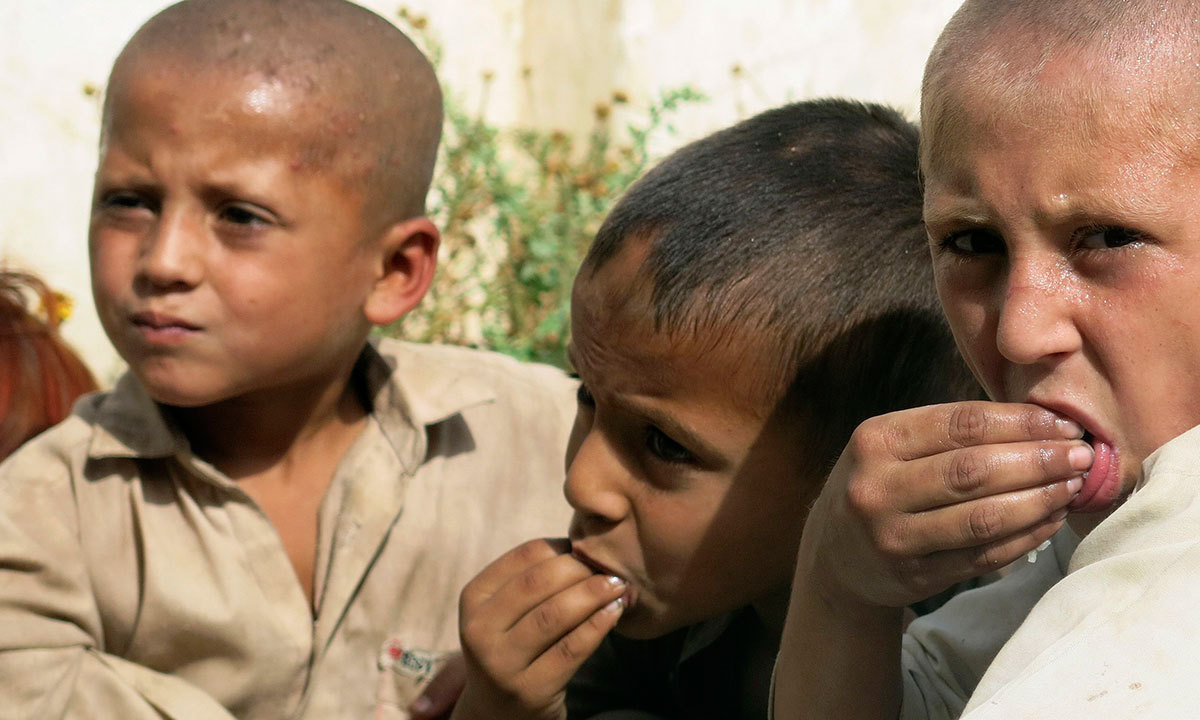 Children fleeing the military offensive against militants in North Waziristan eat their meal while taking refuge with their families in a school building in Bannu. — Photo by Reuters
