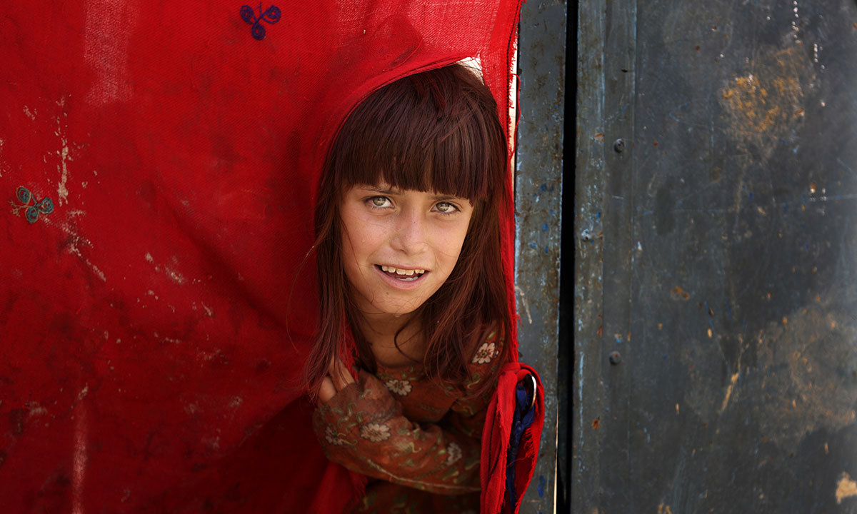 A tribal girl peeks out after fleeing her village in North Waziristan, in Bannu, June 17, 2014. — Photo by AP