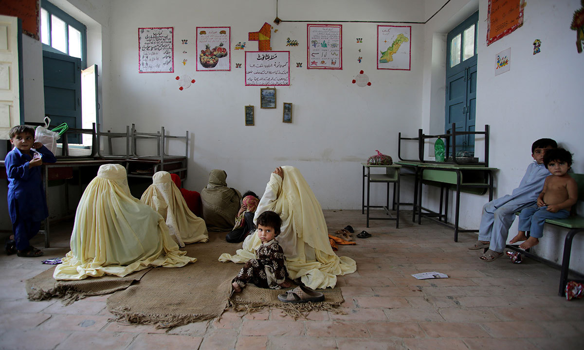 Families take shelter at a school after fleeing from North Waziristan, in Bannu, June 17, 2014. — Photo by AP