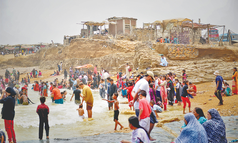 People at Paradise Point head into the rough sea despite a ban on going into the water and several warnings from lifeguards.—Fahim Siddiqi / White Star