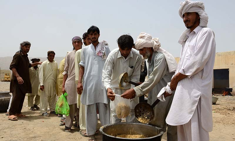 Civilians, fleeing from a military operation in North Waziristan tribal agency, receive food at the Bannu Frontier Region registration centre for internally displaced people in Saidgai on June 22, 2014. — Photo by AFP