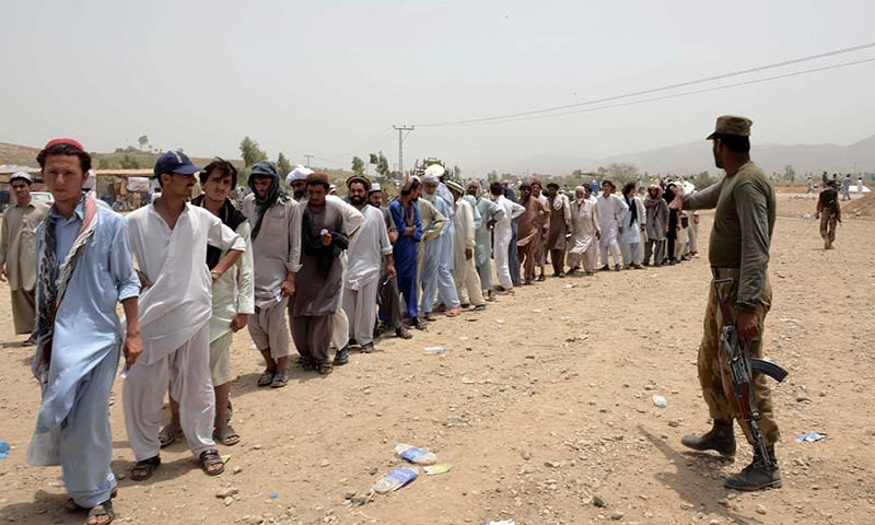 Civilians, fleeing from a military operation in North Waziristan tribal region, wait in line at the Bannu Frontier Region registration centre for internally displaced people in Saidgai on June 22, 2014. — Photo by AFP