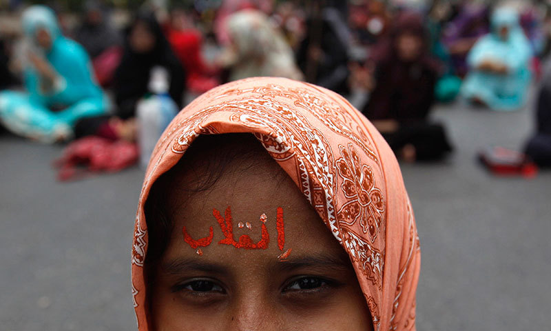 """A supporter of Tahirul Qadri adorns her forehead with the word """"Inqilab"""". — Photo by Reuters"""