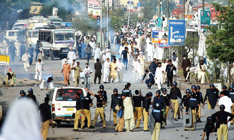 Police and PAT activists clash on a main road in Islamabad. — Photo by Ishaque Chaudhry