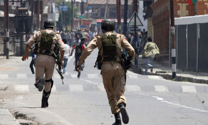 Indian policemen chase Kashmiri protesters in Srinagar. — File Photo by AP