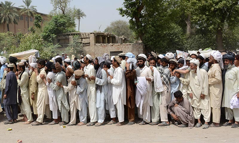 Internally displaced persons from the North Waziristan tribal region queue outside a World Food Programme (WFP) food distribution point in Bannu on June 24, 2014. — Photo by AFP