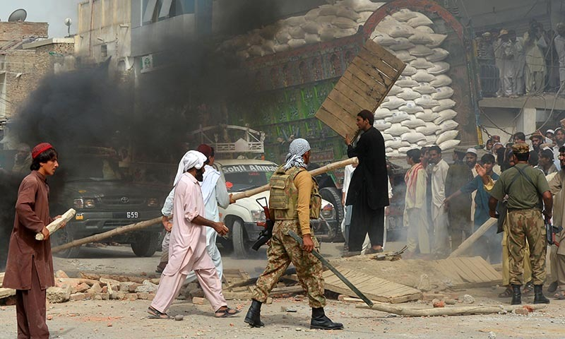 Pakistan Army personnel try to break up a protest by internally displaced presons from the North Waziristan tribal region outside a World Food Programme (WFP) food distribution point in Bannu on June 24, 2014. — Photo by AFP