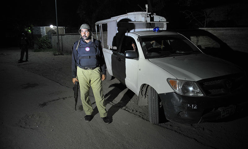Policemen stand guard at a check point outside the Bacha Khan International Airport in Peshawar on June 25, 2014 after an attack on a Pakistan International Airlines flight. — Photo by AFP