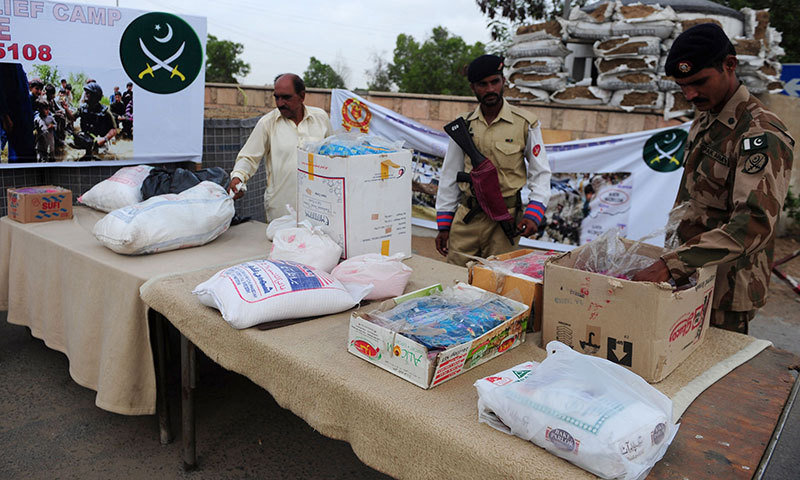 Pakistan army soldiers sort relief goods for the internally displaced civilians, fleeing the military operation against militants of North Waziristan region, at a warehouse in Karachi on June 25, 2014. — Photo by AFP