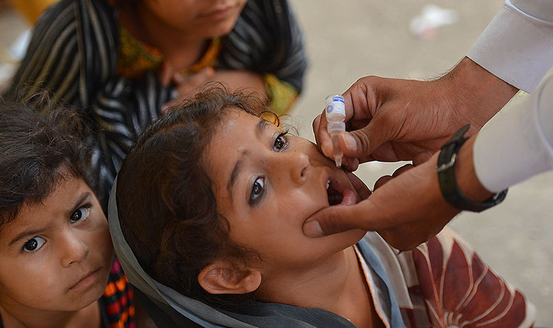 A health worker administers the polio vaccine to a child during a vaccination campaign in Bannu on June 25, 2014. — Photo by  AFP