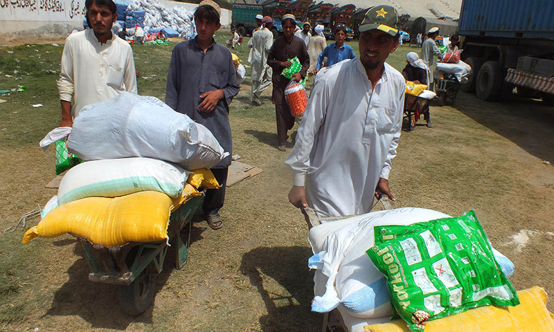 IDPs push their wheelbarrows loaded with relief supplies at the WFP distribution point in Bannu on June 26, 2014. – AFP Photo
