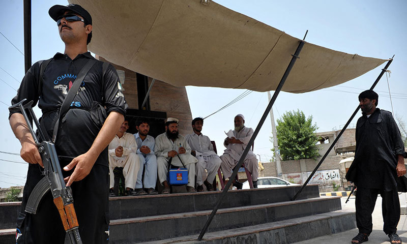 Pakistani police commandos guard a polio vaccination team at a security checkpoint in Bannu on June 26, 2014. — Photo by AFP